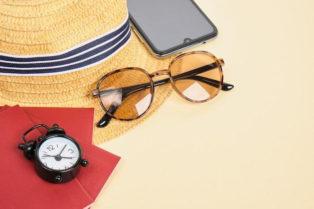 Cappello di paglia, occhiali da sole, sveglia e passaporto su sfondo beige, tempo per il viaggio e concetto di vacanza al mare