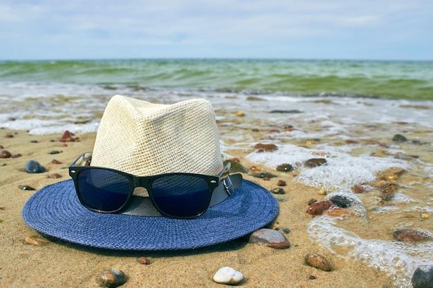 Cappello di paglia e occhiali da sole si trovano su una spiaggia sabbiosa con ciottoli.