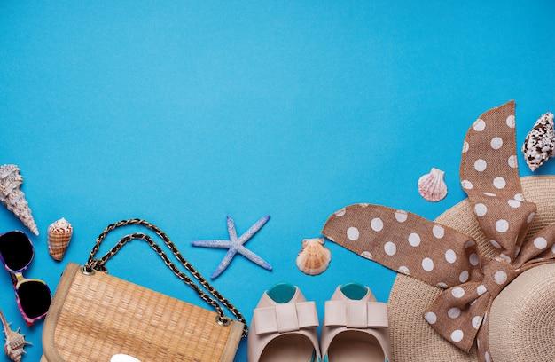 Cappello di paglia, occhiali da sole e scarpe su sfondo blu