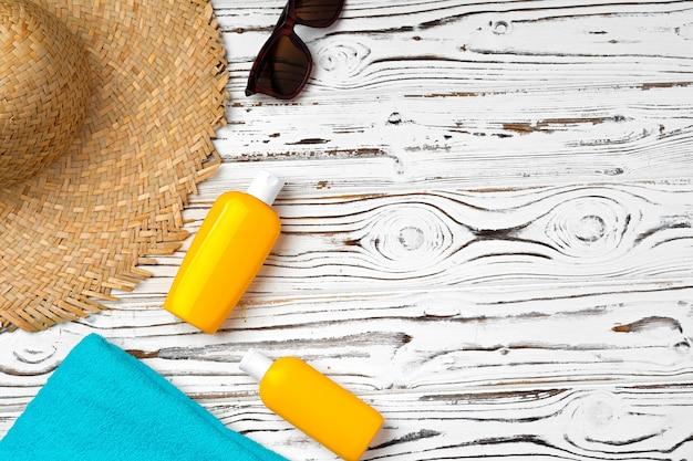 Cappello di paglia, occhiali da sole e bottiglia di crema solare su fondo in legno