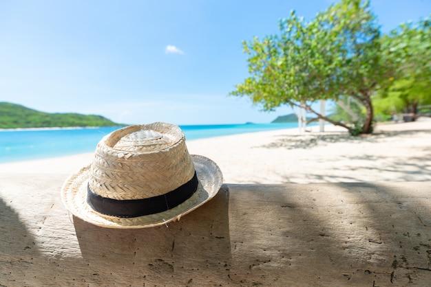 Cappello di paglia sul legname con il fondo fresco del cielo della spiaggia e della spiaggia. concetto di vacanze e vacanze. concetto di relax e relax.