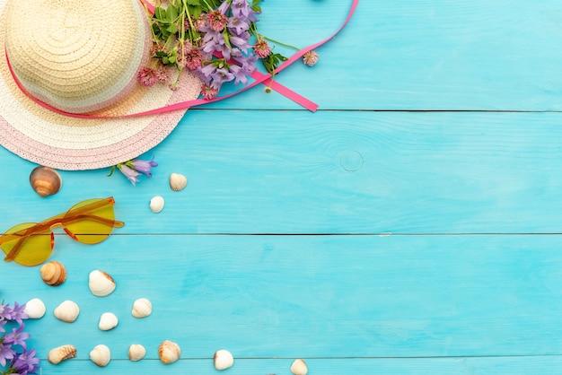 Un cappello di paglia con conchiglie e occhiali da sole su uno sfondo di legno blu.
