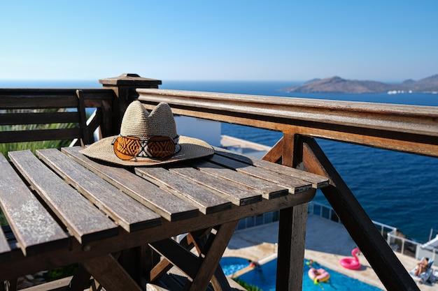 Cappello di paglia con occhiali da sole sulla terrazza in legno della villa vista piscina.