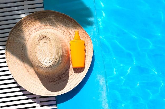 Cappello di paglia con bottiglia di crema solare vicino alla superficie della piscina blu chiaro