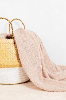 Cesto di vimini paglia con soffice coperta beige, primo piano. elegante oggetto di arredamento per la casa ecologico hygge