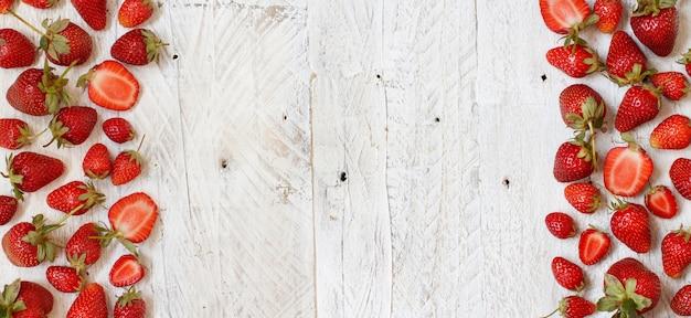 Le fragole si chiudono su su una tavola di legno bianca