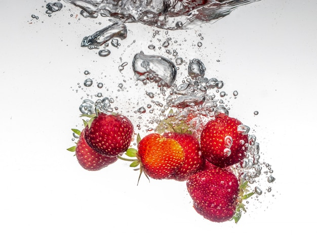 Fragole che cadono in acqua
