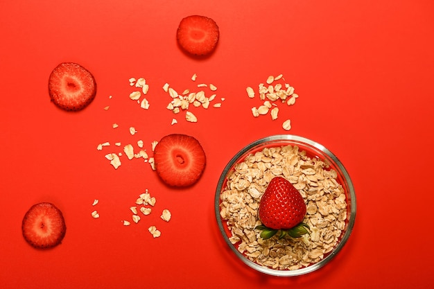 Fragole e fiocchi d'avena su fondo rosso