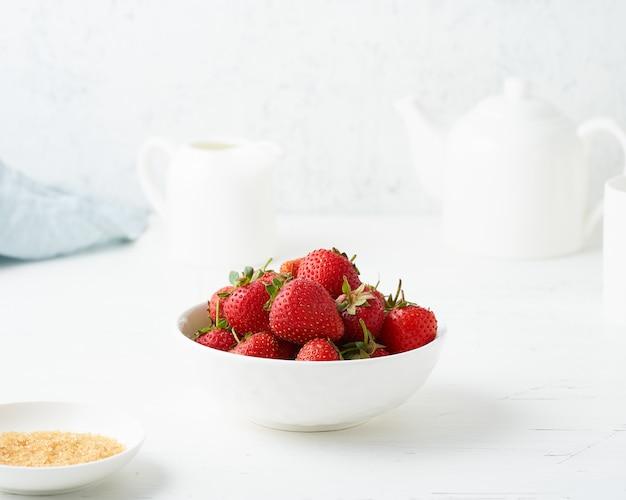 Fragole in una ciotola bianca, sul tavolo bianco, colazione del mattino, cibo estivo