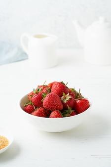Fragole in una ciotola bianca sul tavolo bianco
