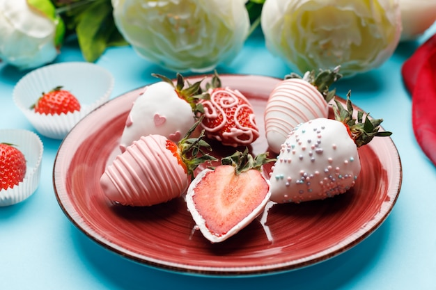 Fragole al cioccolato bianco su un piatto bordeaux