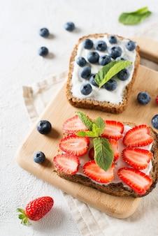 Toast alla fragola e mirtillo a colazione su sfondo bianco. cibo salutare