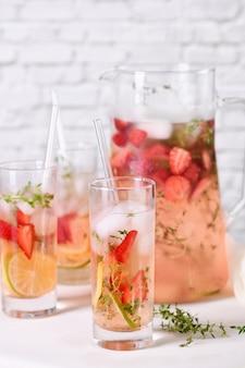 Cocktail alla fragola o limonata con timo e bevanda biologica al limone con frutti di bosco maturi in un bicchiere