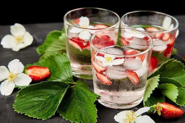 Acqua detox alla fragola con fiori di gelsomino. bevanda ghiacciata estiva