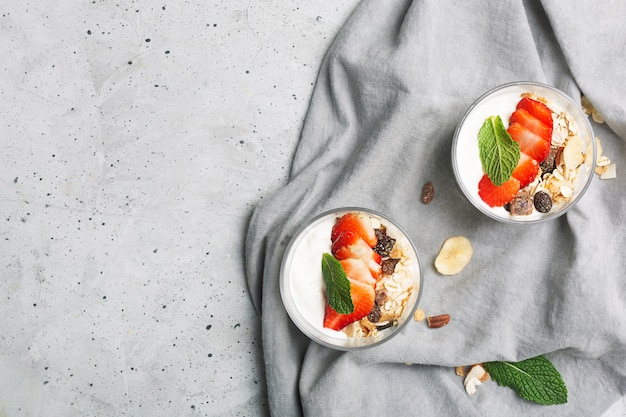 La fragola e il muesli nello yogurt. ciotole di vetro con panna e fragole. vista dall'alto
