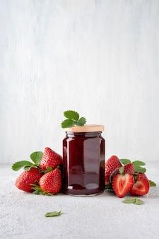 Confettura di fragole in barattolo di vetro e pezzi di fragola. conservare. conservazione domestica, preparazione del cibo.
