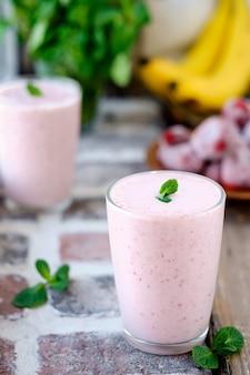Frullato o frappè di fragole, latte e banana in un bicchiere, decorato con una foglia di menta. messa a fuoco selettiva sulla menta. cibo sano o snack, primo piano