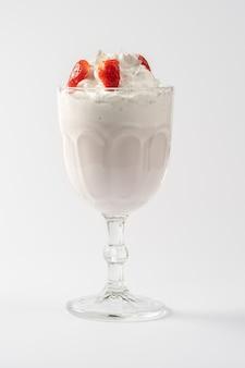 Frullato di proteine del latte alla fragola, con panna montata e sciroppo di fragole su un piatto bianco.