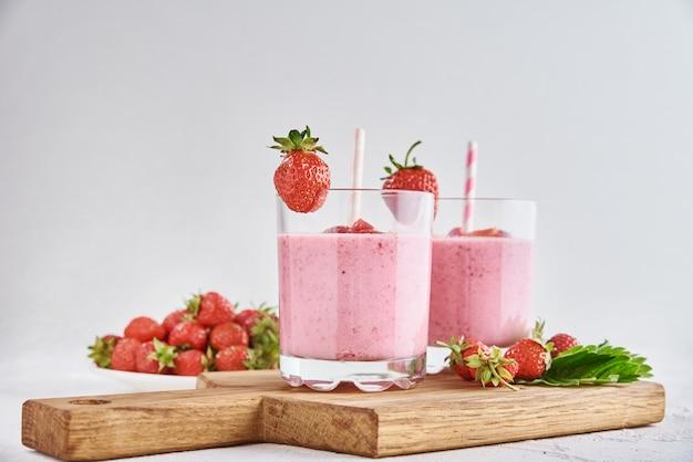 Milk shake alla fragola in vetro con paglia e frutti di bosco freschi