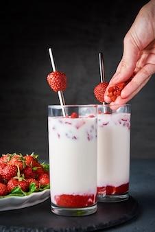 Frullato di latte alla fragola in vetro con paglia e frutti di bosco freschi sul nero