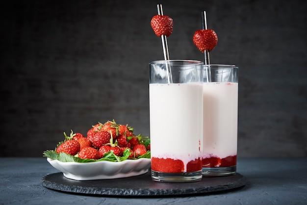 Frullato di latte alla fragola in vetro con paglia e frutti di bosco freschi su oscurità