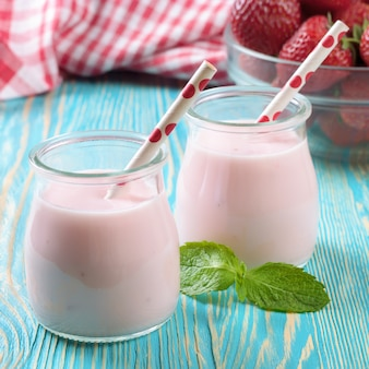 Milkshake alla fragola nel barattolo di vetro con cannuccia sulla tavola di legno blu