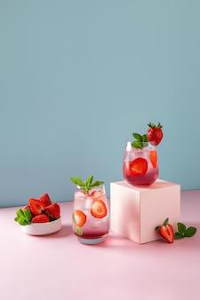 Mojito alla fragola su sfondo blu e podio rosa. bevanda estiva rinfrescante con copia spazio