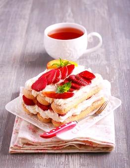 Torta di fragole, pesche, crema con biscotti savoiardi Foto Premium