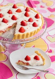 Torta di fragole a fette con crema bianca su una romantica tovaglia rosa decorata con cuori per san valentino.