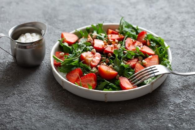 Insalata di fragole con rucola su un piatto con una forchetta su sfondo grigio chiaro