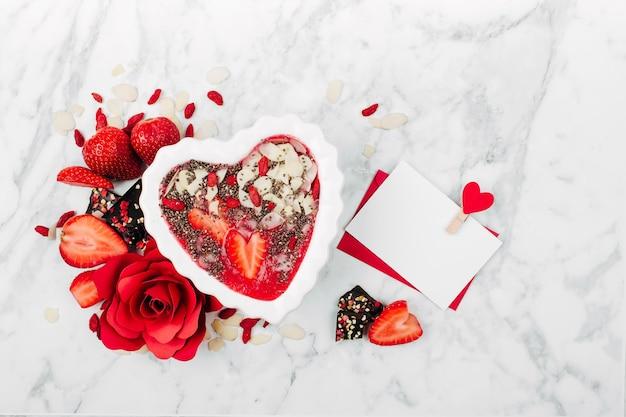 Frullato di fragole in una ciotola a forma di cuore e biglietto di san valentino