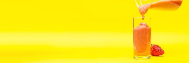 Frullato di fragole, processo di cottura su sfondo giallo, frullato fatto in casa, frullato di vetro.