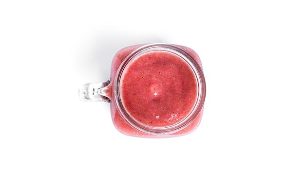Frullato di fragole isolato su bianco. bicchiere con frullato rosa.