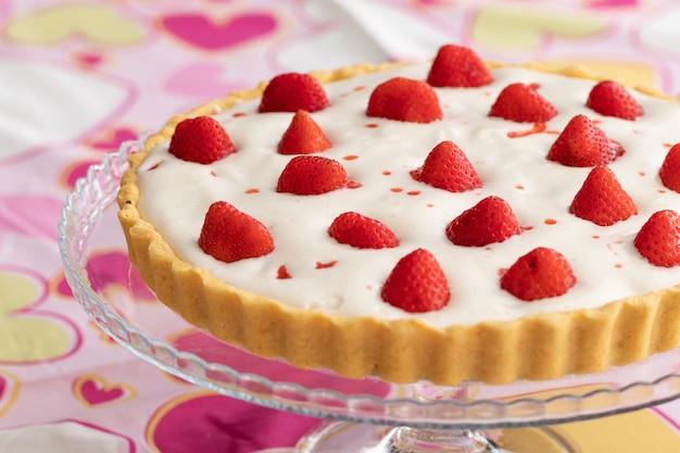 Crostata di fragole con crema bianca su una romantica tovaglia rosa decorata con cuori per san valentino.
