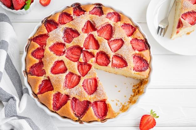 Pan di spagna alla fragola alla vaniglia o torta su un fondo di legno bianco con fragole fresche. dolce estivo. copia spazio.