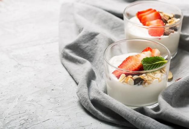 La fragola nello yogurt. ciotole di vetro con panna e fragole, muesli. vista dall'alto