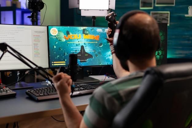 Streamer uomo che parla con più giocatori in cuffia e vince la competizione di videogiochi. giocatore professionista in streaming di videogiochi online con nuova grafica su un potente computer dalla sala da gioco