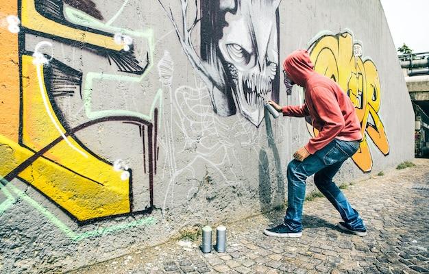 L'artista di strada che dipinge graffiti colorati sulla parete generica