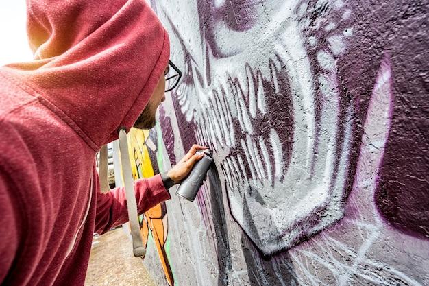 L'artista di strada dipinge graffiti colorati sul muro pubblico