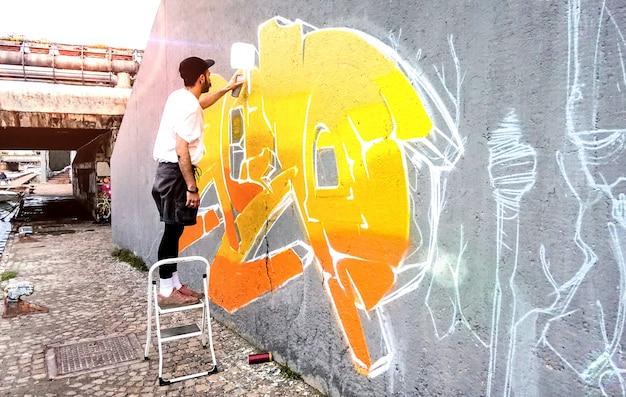 Artista di strada che lavora su graffiti colorati a parete dello spazio pubblico