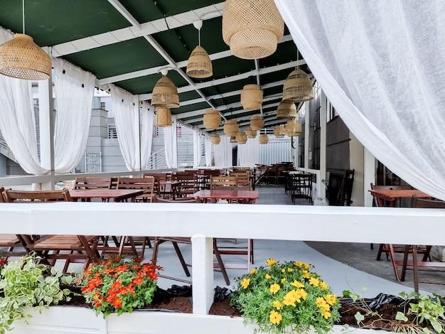 Caffè all'aperto in assenza di persone. quarantena. tavoli e sedie in legno vuoti sulla strada fuori da un bar caffetteria o ristorante con raggi di sole, lampade di paglia il concetto di amore e cena romantica