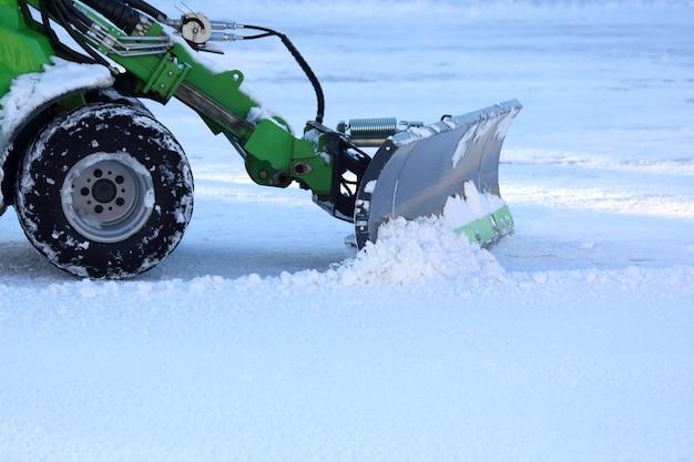 Pulizia delle strade della città dalla neve con l'aiuto di attrezzature speciali mini