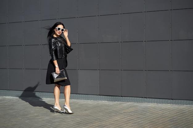 Look alla moda di strada. bella giovane donna in eleganti occhiali da sole che indossa un abito elegante e alla moda giacca di pelle con frange nera tenendo la frizione nelle mani.