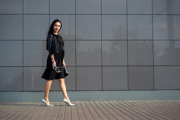 Look alla moda di strada. giovane donna graziosa che porta vestito nero elegante e giacca di pelle con frange nera alla moda che tiene gli occhiali da sole alla moda nella mano. muro urbano su copia spazio.