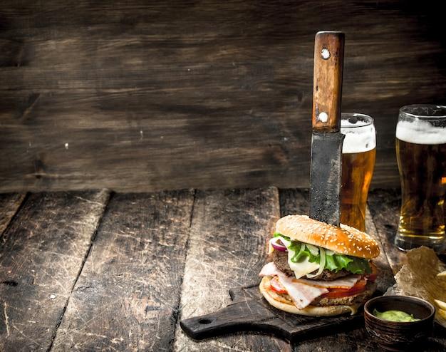 Cibo di strada un grande hamburger con birra su uno sfondo di legno