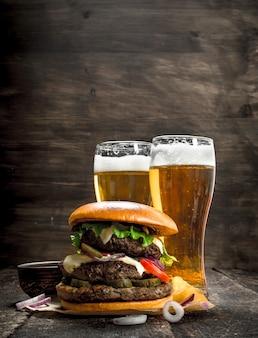 Cibo di strada un grande hamburger con bicchieri di birra leggera su uno sfondo di legno