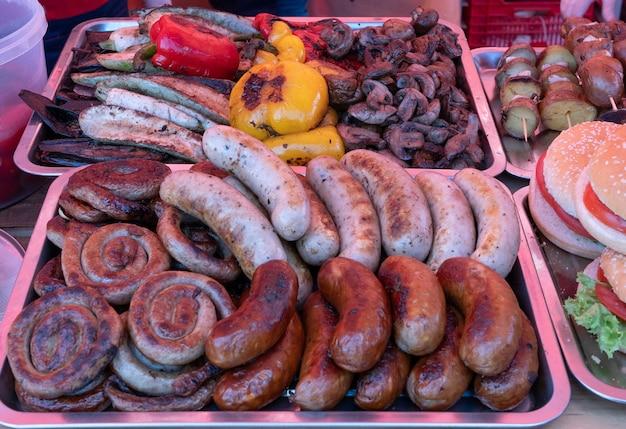 Cibo di strada al mercato di campagna - salsicce barbecue alla griglia?