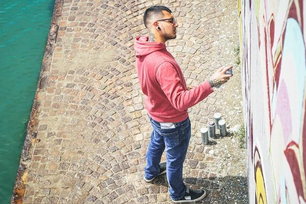 La pittura di artista di graffiti di strada con una bomboletta di colore può un murale di graffiti sul muro