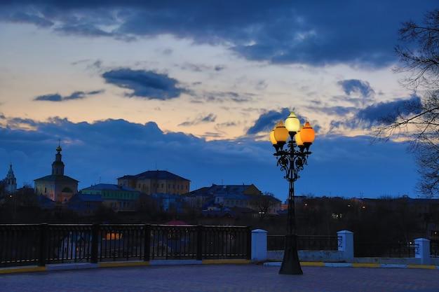 Lampione sullo sfondo di un bel cielo al tramonto con nuvole case colorate e chiesa