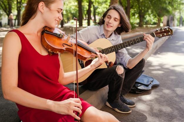 Gruppo di duo di musica di strada che si esibisce in un parco. spiriti liberi concetto di romanticismo hippie free